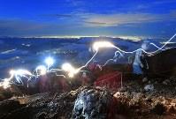 日の出を拝もうと山頂を目指す登山者のヘッドライトの光跡=山梨県富士吉田市の富士山吉田口8合目で2018年6月30日午後7時52分、手塚耕一郎撮影(30秒露光)