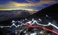 7月1日の山開きを前に、富士山に登る人たち(60秒露光)=富士山吉田口八合目付近で2018年6月30日午後8時2分、玉城達郎撮影