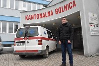 Alen Muhic stands in front of the hospital where he works as a medical assistant, in Gorazde in southeastern Bosnia and Herzegovina. He was born -- and abandoned -- at the hospital during the Bosnian conflict in 1993. (Mainichi)