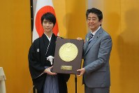 Figure skater Yuzuru Hanyu, left, receives the People's Honor Award from Prime Minister Shinzo Abe at the latter's office, on July 2, 2018. (Mainichi)