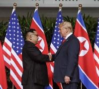 握手する米朝の両首脳=シンガポールで2018年6月12日、AP共同