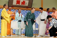 Rakugo storyteller Katsura Utamaru, center, leaves the stage to the applause of other members of the Japanese comedy TV show