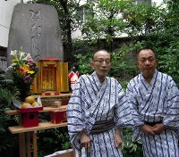 Rakugo storyteller Katsura Utamaru, left, poses with Sanyutei Koyuza for a photo on Aug. 31, 2015, in front of Hanashizuka, a monument for stories which were prohibited to be performed during wartime. (Mainichi)