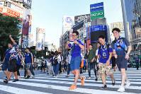日本の敗戦に悔しい表情で、渋谷駅前の交差点を渡るサポーターら=東京都渋谷区で2018年7月3日午前5時33分、渡部直樹撮影