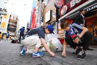 ベルギー戦後、歩道のゴミを片付ける日本のサポーターたち=東京都渋谷区で2018年7月3日午前6時1分、渡部直樹撮影