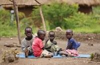 コップ1杯の穀物の1種・ソルガムを食べる難民の兄弟。父を紛争で亡くし、母は日中キャンプ内のマーケットで働くため、昼食は年長のアレックス君(7=左端)の仕事だ。テントの前にゴザをしき、コップを囲んで分け合いながら、少しずつ口に運んだ=ウガンダ・アルアで2018年4月8日、小川昌宏撮影