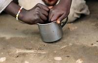 コップ1杯のソルガムを分け合って食べる難民の兄弟。父を紛争で亡くし、母は日中キャンプ内のマーケットで働くため、昼食は年長の兄が弟の面倒を見ていた=ウガンダ・アルアで2018年4月8日、小川昌宏撮影