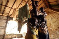 国内避難民の保護区で、テントから外を見つめるユンミス・コール君(手前左)、ユンブニ・コール君(手前右)の家族。暗いテント内に不安げな表情が浮かんだ=南スーダン・ジュバで2018年4月17日、小川昌宏撮影