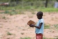 難民キャンプの小学校で、ノートを広げる少女。ノートにはカバーがつけられ、大切に使っているようだった=ウガンダ・ユンベで2018年4月6日、小川昌宏撮影
