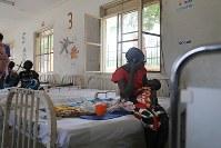 重度の栄養失調となり、やせ細ったアチョコ・マトゥワちゃん(2)。暗い病室で、母アゴック・クウェックさん(20)は骨と皮だけになったアチョコちゃんを抱き寄せた=南スーダン・ジュバで2018年4月24日、小川昌宏撮影