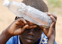 難民キャンプの小学校で、疲れた表情を浮かべるアゴゴ・サベットくん(6)。ペットボトルには筆記用具が入っていた=ウガンダ・ユンベで2018年4月6日、小川昌宏撮影