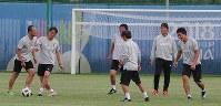 和やかな雰囲気でボール回しをする西野監督(右から2人目)とコーチ陣=ロシア・カザンで2018年7月3日、長谷川直亮撮影
