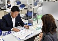 窓口で接客する中井隆盛さん=仙台市宮城野区の七十七銀行扇町支店で