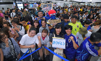 Fans wait for Japanese national soccer team members who returned from the World Cup in Russia at Narita International Airport in Narita, Chiba Prefecture, on July 5, 2018. (Mainichi)