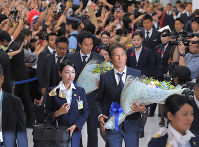 Fans welcome Japan soccer team head coach Akira Nishino, front center, captain and midfielder Makoto Hasebe, front left, and other team members at Narita International Airport in Narita, Chiba Prefecture, on July 5, 2018, after they returned from the World Cup in Russia. (Mainichi)
