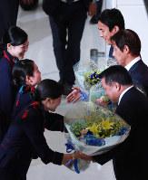 Staff members at Narita International Airport offer flowers to Japan Football Association President Kohzo Tashima, bottom right, Japan soccer team head coach Akira Nishino, center, and captain and midfielder Makoto Hasebe at the airport on July 5, 2018. (Mainichi)