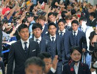 Fans welcome Japan soccer team midfielder Shinji Kagawa, center, goalkeeper Eiji Kawashima, left, and other team members at Narita International Airport in Narita, Chiba Prefecture, on July 5, 2018, after they returned from the World Cup in Russia. (Mainichi)