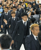 Japan national soccer team members wave to fans at Narita International Airport in Narita, Chiba Prefecture, after returning from the World Cup in Russia on July 5, 2018. (Mainichi)