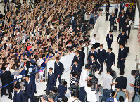 A large number of fans welcome Japan national soccer team members at Narita International Airport in Narita, Chiba Prefecture, on July 5, 2018, after they returned from the World Cup in Russia. (Mainichi)