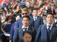 Fans welcome Japan soccer team forward Shinji Okazaki, front center, defender Gen Shoji, right, midfielder Keisuke Honda, back center, and other members at Narita International Airport in Narita, Chiba Prefecture, after they returned from the World Cup in Russia on July 5, 2018. (Mainichi)