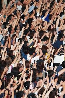 W杯ロシア大会から帰国した日本代表の選手たちを撮影しようと、いっせいにスマートフォンを向けるサポーターら=成田空港で2018年7月5日午前11時13分、玉城達郎撮影