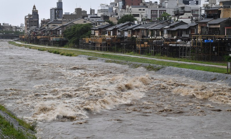 The swollen Kamo River is seen following heavy rain near the Sanjo Ohashi Bridge in Kyoto