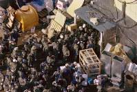 山梨県上九一色村(現富士河口湖町)にあるオウム真理教の教団施設の家宅捜索で、第6サティアンに入る大勢の警視庁の捜査員たち。捜査員は自衛隊から貸与された戦闘用防護衣を着用している=上九一色村で1995年3月22日、本社ヘリから