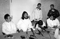 AUM Shinrikyo cult founder Chizuo Matsumoto, also known as Shoko Asahara, center, appears at a news conference with Kiyohide Hayakawa, left, Tomomitsu Niimi, center back, and other followers who implemented his orders, on Nov. 30, 1989. (Mainichi)