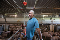豚小屋を案内するマーク・マクハーグさん=米中西部ネブラスカ州セントラルシティーで2日、ルーベン・モナストラ撮影