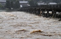 大雨で増水し、渡月橋に迫る桂川の濁流=京都市右京区で2018年7月5日午後5時59分、川平愛撮影