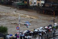 水かさが増した鴨川を四条大橋から眺める人たち=京都市東山区で2018年7月6日午後4時35分、川平愛撮影