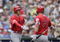 Los Angeles Angels' Shohei Ohtani, left, is greeted by Mike Trout after scoring against the Seattle Mariners during the fourth inning of a baseball game on July 4, 2018, in Seattle. (AP Photo/John Froschauer)