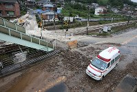 An ambulance passes by a railway crossing inundated by muddy flood waters from heavy rain, in Mihara, Hiroshima Prefecture, on July 7, 2018. (Mainichi)