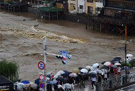 People look at the swollen Kamo River from Shijo Ohashi Bridge following heavy rain in Kyoto's Higashiyama Ward, on July 6, 2018. (Mainichi)