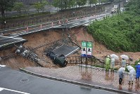 A portion of National Route No. 201, which collapsed, and two cars that plunged from the road are seen in Iizuka, Fukuoka Prefecture, on July 6, 2018, following heavy rain. (Mainichi)