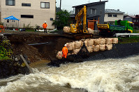 Sandbags are stacked on a damaged bank of the Sunori River running through the city of Takayama, Gifu Prefecture, on July 6, 2018. The road along the river also collapsed and water supply pipelines were damaged. (Mainichi)