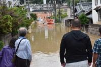 消防士らがボートで住人を避難させる様子を心配そうに見つめる住民=広島県坂町で2018年7月7日午前8時32分、小山美砂撮影