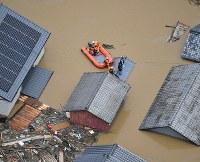 小田川が決壊し、洪水になった町で続けられる救助作業=岡山県倉敷市真備町で2018年7月7日午後0時8分、本社ヘリから加古信志撮影