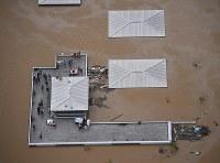 川の決壊で濁流であふれた町。屋上には多くの住人が避難している=岡山県倉敷市真備町で2018年7月7日午後0時37分、本社ヘリから加古信志撮影