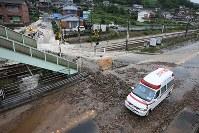 濁流で壊れた踏み切りそばを通る救急車=広島県三原市で2018年7月7日午前10時40分、小出洋平撮影