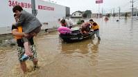 水浸しになった町で、救助される住民ら=岡山県倉敷市真備町で2018年7月7日午後5時51分、望月亮一撮影