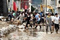 道路に流れ込んだ土砂を撤去する人たち=広島市安佐北区で2018年7月7日午後5時27分、幾島健太郎撮影