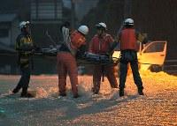 集中豪雨で道路を水が流れて孤立した地区で、お年寄りを担架に乗せて搬送する消防隊員ら=広島市安芸区矢野東で2018年7月7日午後7時36分、手塚耕一郎撮影
