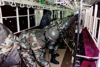 サリンが散布された地下鉄丸ノ内線の車内を、防護マスクを着用しデッキブラシを使って除染、洗浄する陸上自衛隊の除染部隊=東京都文京区の地下鉄丸ノ内線後楽園駅で1995年3月20日、陸自提供