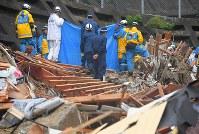土砂崩れで家が流された現場で、遺体が見つかり、現場をブルーシートで覆う警察官ら=広島市安芸区矢野東で2018年7月8日午後2時44分、手塚耕一郎撮影