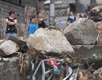 土砂崩れで巨岩が転がる中、石を投げて遊ぶ子供たち=広島市安芸区矢野東で2018年7月8日午後3時27分、手塚耕一郎撮影