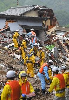 土砂崩れで家が流された現場で、重機が入れず手作業で行方不明者を捜索する消防隊員ら=広島市安芸区矢野東で2018年7月8日午後0時58分、手塚耕一郎撮影