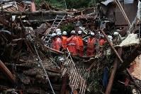 押し流され倒壊した民家を捜索する消防隊員=広島県呉市で2018年7月8日午後3時58分、小出洋平撮影