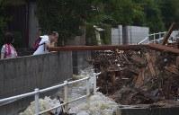 激しく泥水が流れる様子を見つめる男性=広島県呉市天応西条で2018年7月8日午後4時54分、藤井達也撮影