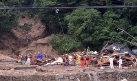 土砂崩れに巻き込まれて倒壊した建物を調べる消防隊員=広島県呉市天応西条で2018年7月8日午後5時31分、藤井達也撮影